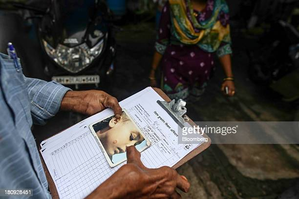 Tulshiram Kshirsagar a paramedical worker for the Bombay Leprosy Project left holds an image of a person with leprosy during a routine field visit to...