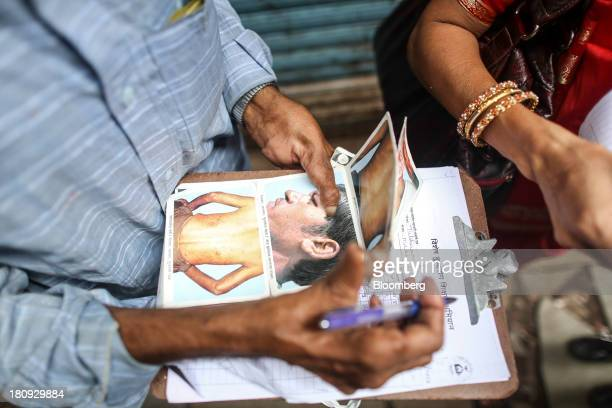 Tulshiram Kshirsagar a paramedical worker for the Bombay Leprosy Project holds images of people with leprosy during a routine field visit to a slum...