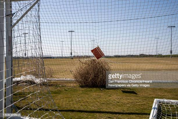 Tumbleweed is seen trapped by a soccer goal net in an empty field, closed due to the ongoing COVID-19 pandemic, at the planned community at River...