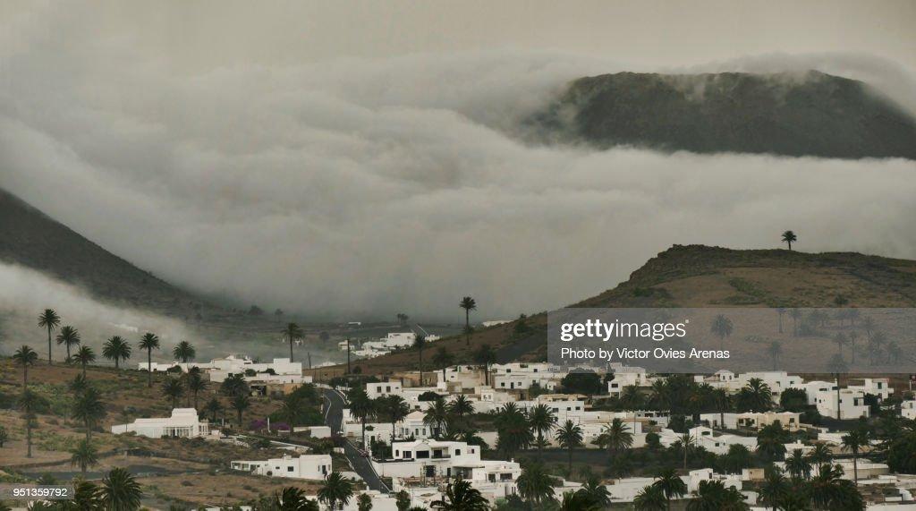 Tumultuous clouds flowing downhill behind the village of Haria in Lanzarote, Canary Islands, Spain : Foto de stock