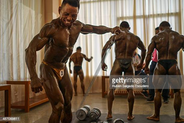 Tun Min of Myanmar works out amongst other athletes before competing in the 55kg bodybuilding contest at the Myanmar Convention Center during the...