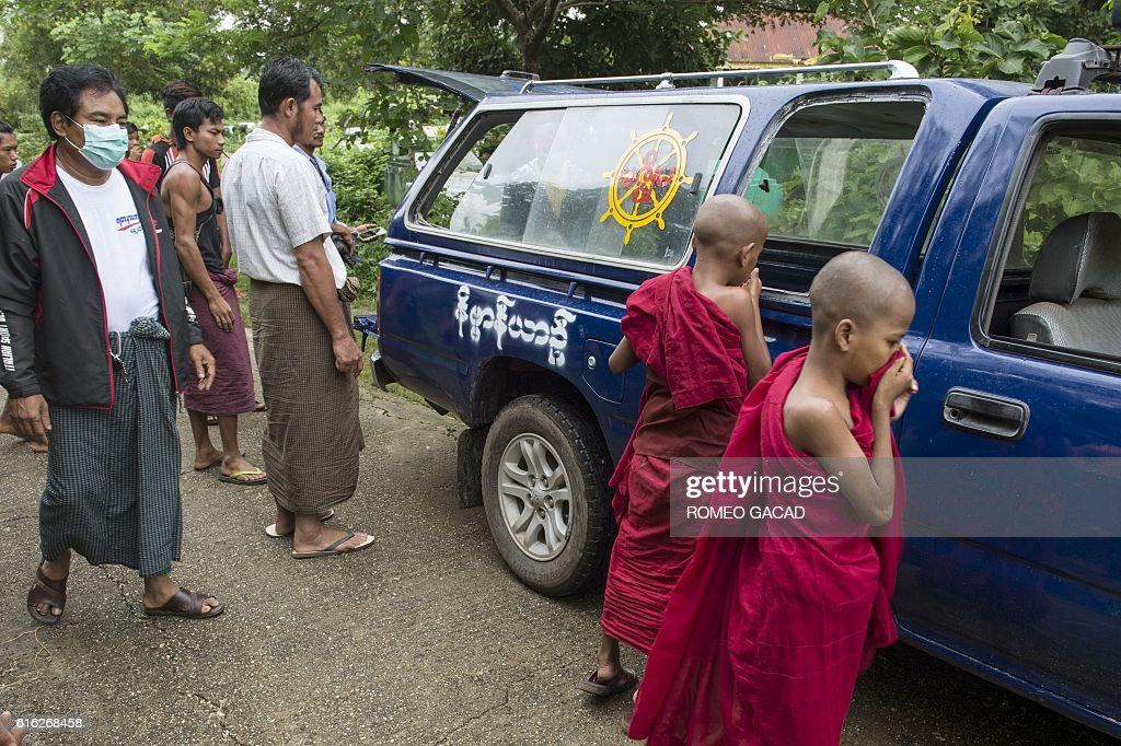 Tun Naing (3rd L in white shirt) looks at hospital workers carry the body of his three-year-old nephew Nay La Linn, a victim of an exorcism ritual, for burial at a public cemetery in Twante town, south of Yangon on October 22, 2016 as young novice monks looks on. Three infant children have been beaten to death in a Myanmar village outside Yangon by a man purporting to be a spiritual healer, who told their families they were possessed by evil spirits. / AFP / ROMEO