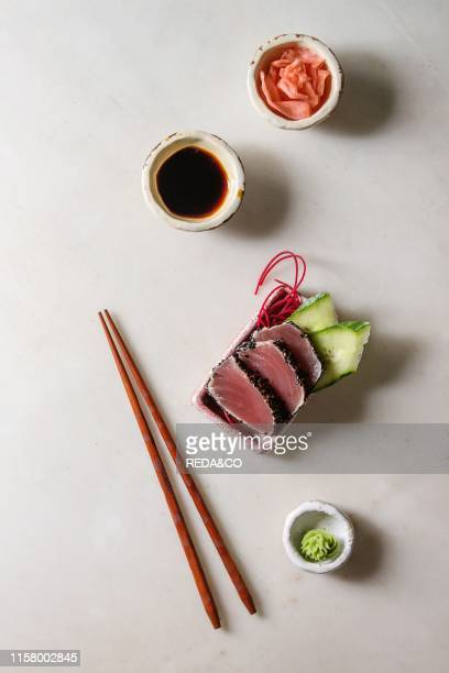 Tuna Sushi sashimi with cucumber in pink ceramic serving plate with chopsticks bowls of soy sauce and pickled ginger cotton flowers over white marble...