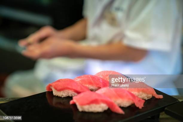 tuna sushi with chef preparing sushi in japanese restaurant. - nigiri stock pictures, royalty-free photos & images