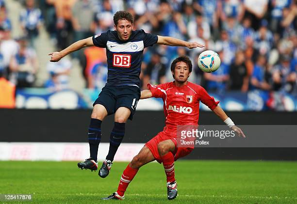 Tunay Torun of Berlin and Hajime Hosogai of Augsburg battle for the ball during the Bundesliga match between Hertha BSC Berlin and FC Augsburg at...