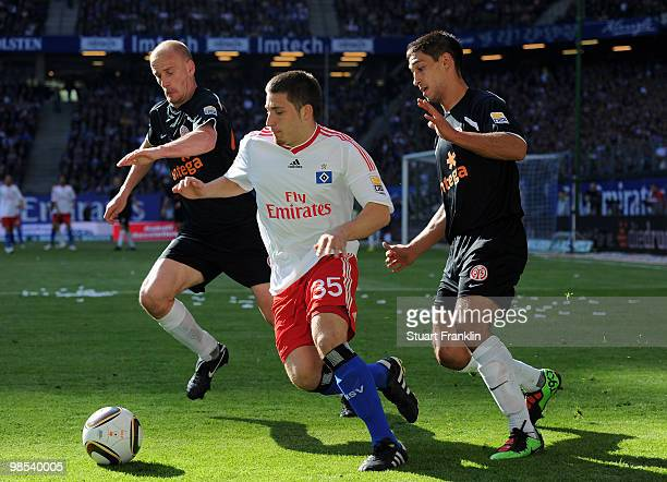Tunay Torun of Hamburg is challenged by Miroslav Karhan and Malik Fathi of Mainz during the Bundesliga match between Hamburger SV and FSV Mainz 05 at...