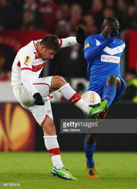 Tunay Torun of Stuttgart is challenged by Katuku Tshimanga of Genk during the UEFA Europa League Round of 32 first leg match between VfB Stuttgart...