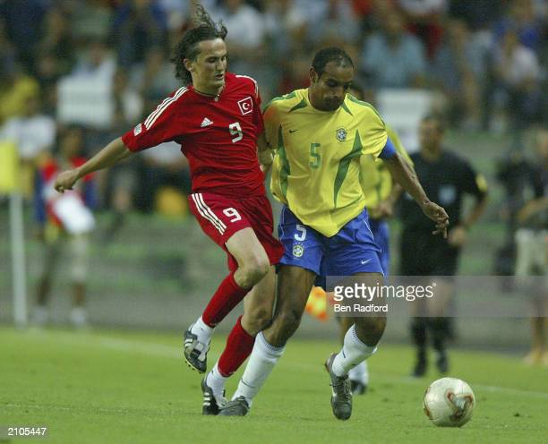 Tuncay Sanli of Turkey and Emerson of Brazil clash during the Confederation Cup Group B match between Brazil and Turkey at the Stade Geoffroy...