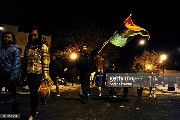 Tunda Asega waives a flag as he marches with others down Washington Street during a Kwanzaa celebration on Monday December 26 2011 AAron Ontiveroz...