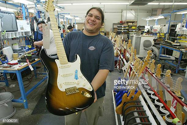 Tunertester Arturo Madrid shows off a new Fender Stratocaster in the style of the 1954 original at the Fender manufacturing facility in Corona...