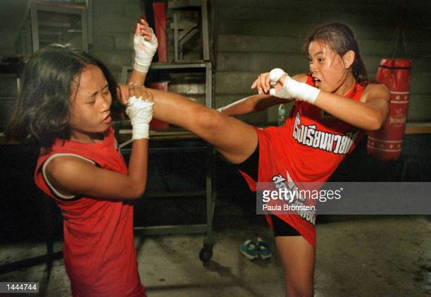 Tung left gets a hard kick by Featherweight champion Muay Thai boxer Rungarun May 2000 during practice at the Muaythai Institute at Rangsit stadium...