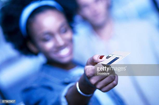 tungsten shot of a young woman holding out a credit card