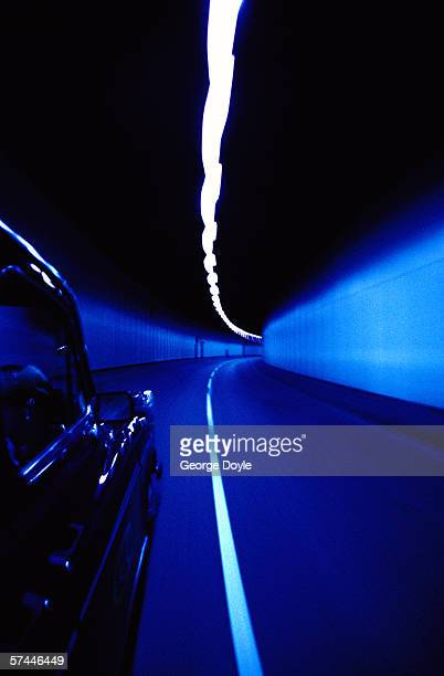 tungsten toned shot of the side of a car driving in a tunnel; blurred