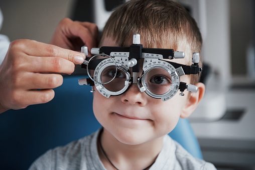 Tuning the intrument. Little boy with phoropter having testing his eyes in the doctor's office 1140521075