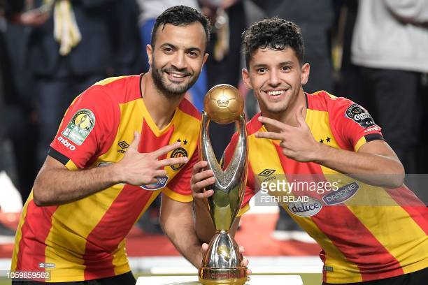 ES Tunis' forward Saad Beguir poses with ES Tunis' forward Taha Yassine Khenissi and the trophy after winning the CAF Champions League second leg...
