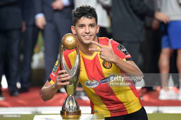 ES Tunis' forward Saad Beguir poses with the trophy after winning the CAF Champions League second leg final football match between Egypt's AlAhly and...