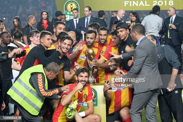 ES Tunis' players celebrate with the trophy after winning the CAF Champions League second leg final football match between Egypt's AlAhly and...