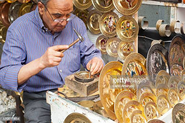 CONTENT] Tunis Tunisia 2013 Craftsman punches out pattern on decorative brass plate at the medina dense agglomeration of alleys and covered passages...