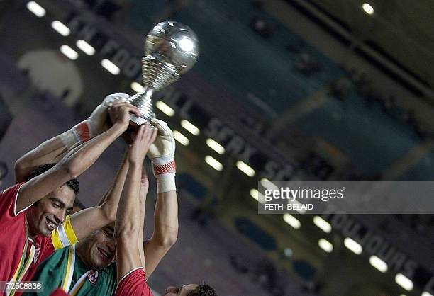 Egyptian AlAhly players captain Mohamed Shady and goalkeeper Essam AlHadary hold up the throphy after winning their second leg of the African...