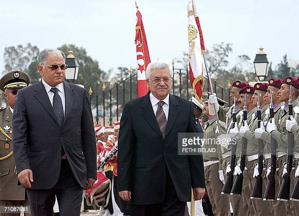 Palestinian president Mahmud Abbas reviews the honour guard with Tunisian Minister of Defence Kamel Morjane in front of the flag of the Sijoumi...