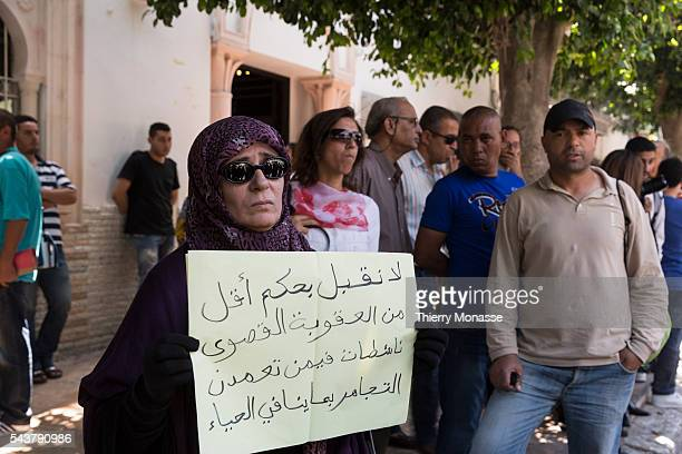 Tunis Tunisie June 12 2013 A woman holds a panel with We demand maximum penalty for Femen activists who intended to cause malice and impurity written...