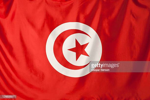 Tunisia flag, red crescent moon and red star shape in a white circle with a red background