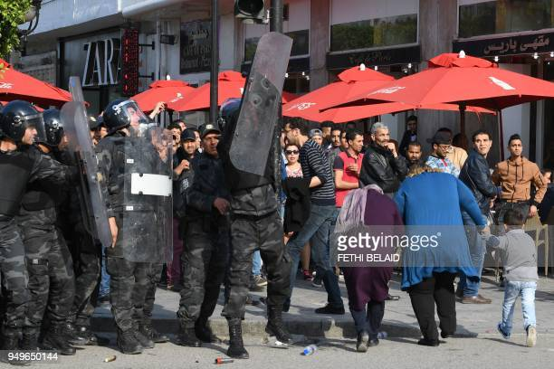 Tunisian anti riot policemen stand guard a street as Club Africain fans demonstrate against the police they accuse of causing the death of a...