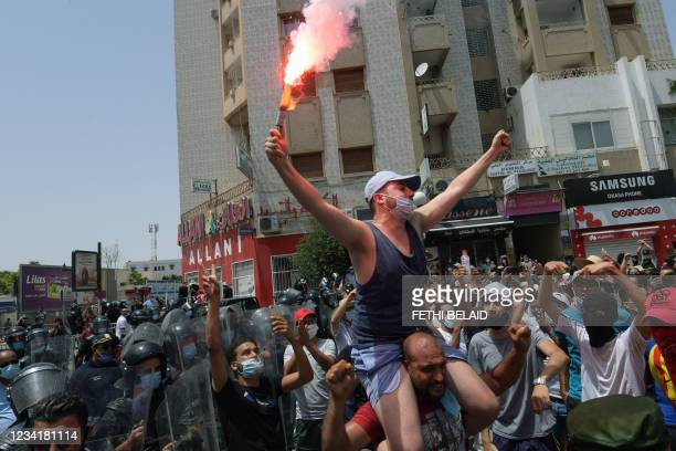 Tunisian anti-government protester holds a flare during a rally in front of the Parliament in the capital Tunis on July 25, 2021.