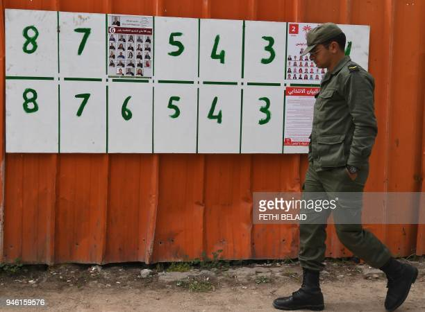A Tunisian army officer walks past lists of candidates for the upcoming municipal elections in the Tunis suburb of Ariana on April 14 2018 Tunisia...