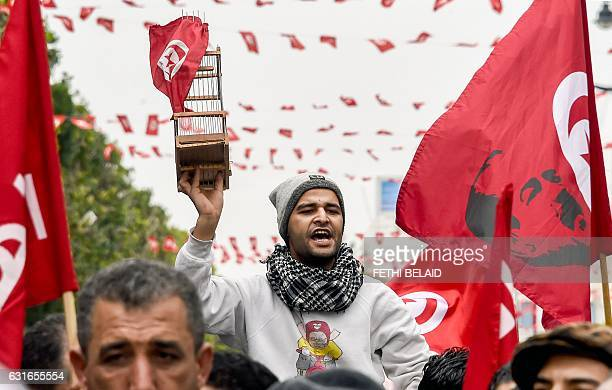 A Tunisian carries a birdcage with the national flag suspended above next to another national flag defaced with a silhouette of of slain prominent...