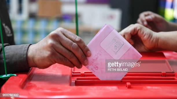 A Tunisian casts his checked ballot in a box as he votes in the first free municipal elections since the 2011 revolution at a polling station in Ben...