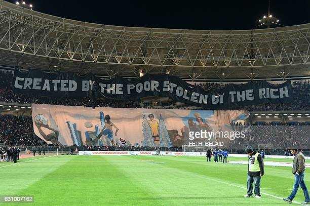 Tunisian Club Africain's supporters display banners before the start of the friendly football match between Club Africain and Paris Saint Germain on...