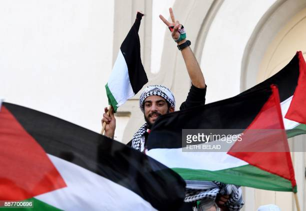 A Tunisian demonstrator flashes the sign for victory and waves the Palestinian flag during a demonstration on December 7 on Habib Bourguiba Avenue in...