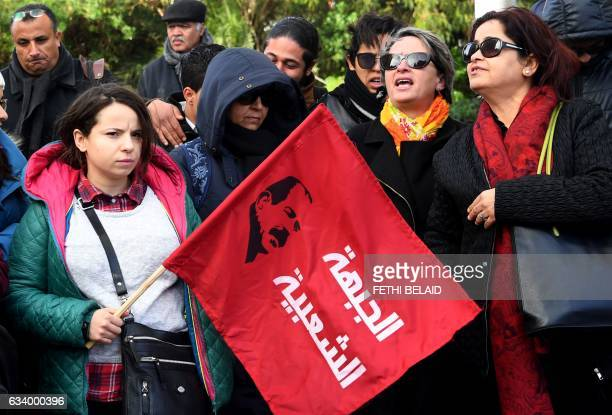 A Tunisian demonstrator holds a flag bearing a portrait of murdered Tunisian opposition figure Chokri Belaid during a gathering marking the fourth...