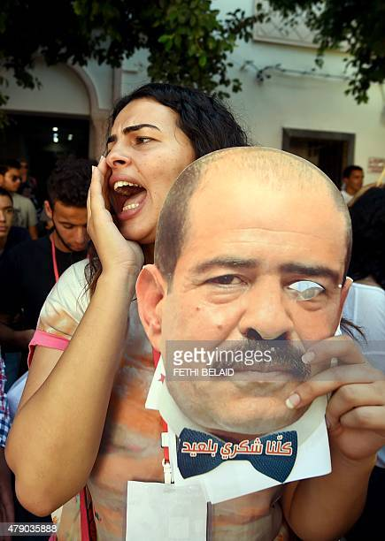 A Tunisian demonstrator holds a picture of murdered prominent Tunisian leftwing opposition leader Chokri Belaid and reading in Arabic we are all...