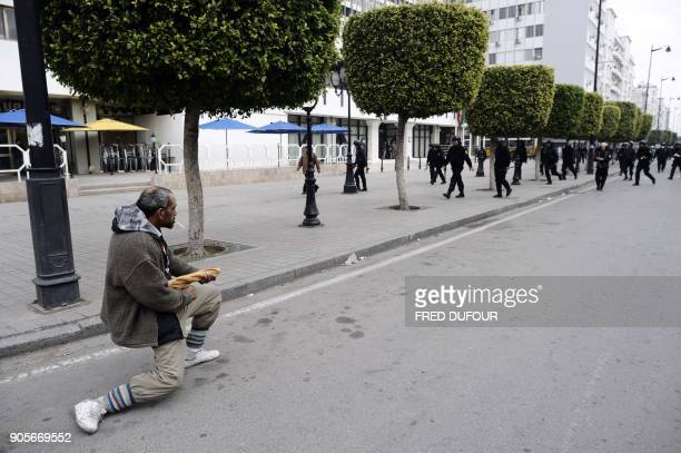 A Tunisian demonstrator holds his bread stick like a weapon in front of riot police during a protest against the country's new government in Tunis on...