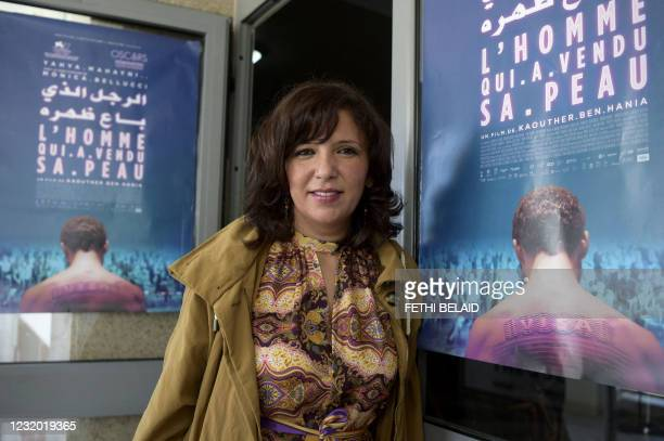 """Tunisian director and screenwriter Kaouther Ben Henia, poses for a picture in front of the poster of her film """"The man who sold his skin"""" during its..."""