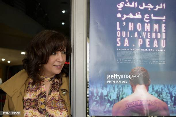 """Tunisian director and screenwriter, Kaouther Ben Henia, poses for a picture in front of the poster of her film """"The man who sold his skin"""" during its..."""