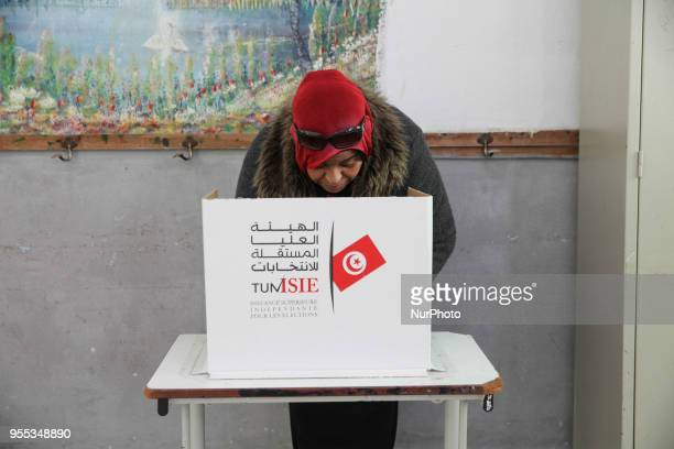 A Tunisian elderly woman casts her vote at a primary school turned into a polling station during the municipal election in Ariana governorate near...