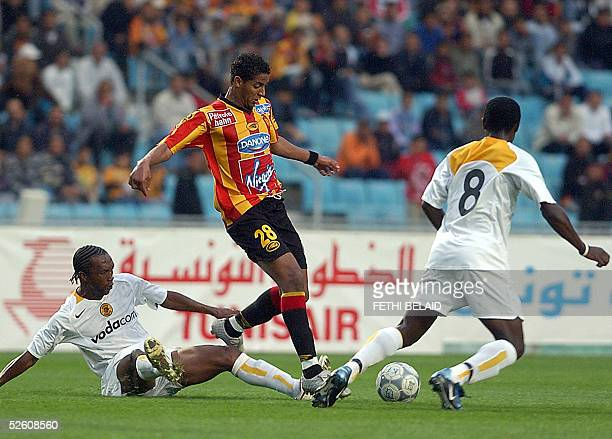 Tunisian Esperance striker Issam Jomaa vies with South Africa defender John Moshoeu and Washington Timashe during their African Champions League...