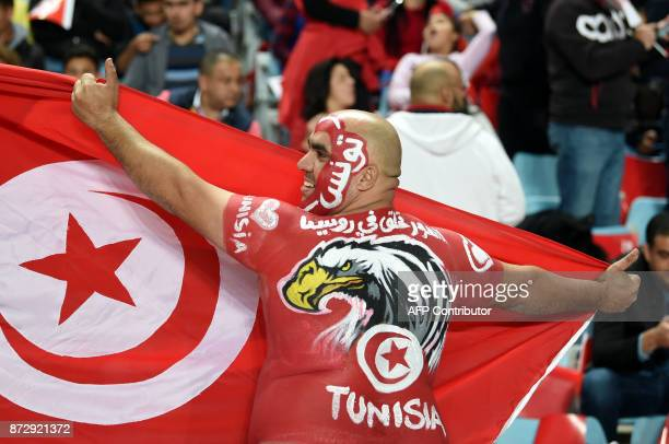 A Tunisian fan cheers for his national team ahead of the FIFA World Cup qualification football match between between Tunisia and Libya at Rades...