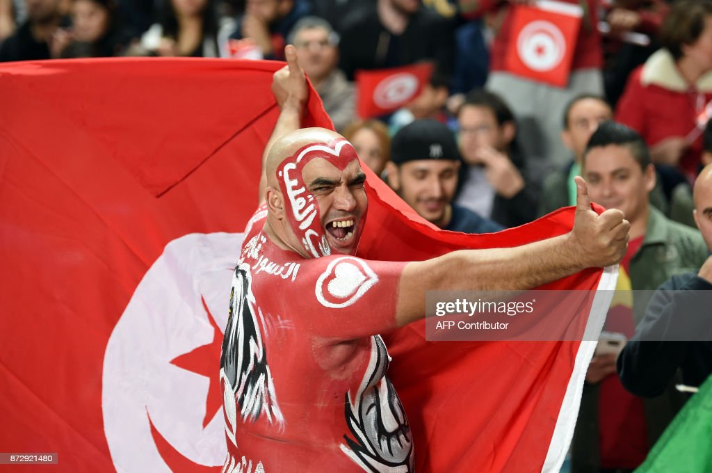 A Tunisian fan cheers for his national team ahead of the FIFA World Cup qualification football match between between Tunisia and Libya at Rades Olympic Stadium on November 11, 2017. /