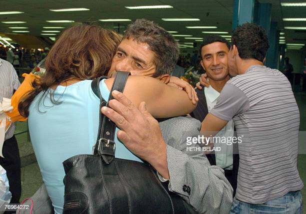 Tunisian fisherman boat captain Abdelkarim Bayouth and Addelbasset Zannuri hug their family upon their arrival 23 September 2007 at the...