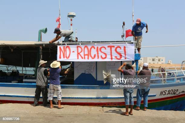 Tunisian fishermen hang banners as they gather on August 6 2017 in the port of Zarzis in southeastern Tunisia to protest against a possible berthing...