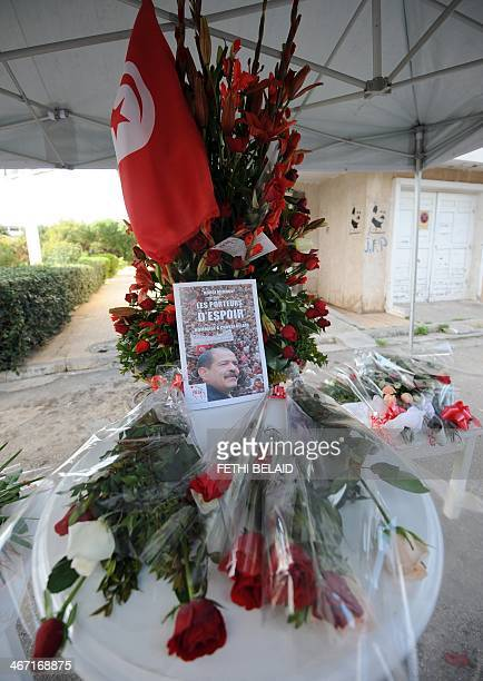 A Tunisian flag and flowers decorate a memorial for slain opposition leader Chokri Belaid erected at the site where he was murdered one year ago on...