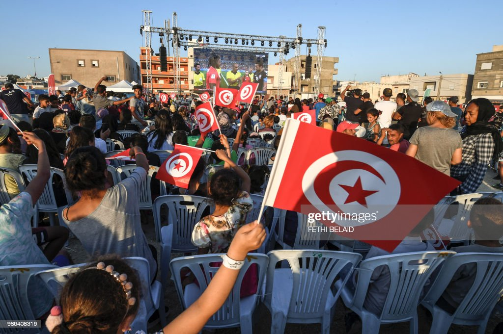TOPSHOT - Tunisian football fans cheer for their national team as they watch the Russia 2018 World Cup Group G match between Tunisia and Panama in the impoverished neighborhood of El-Mellassine in the capital Tunis on June 28, 2018.