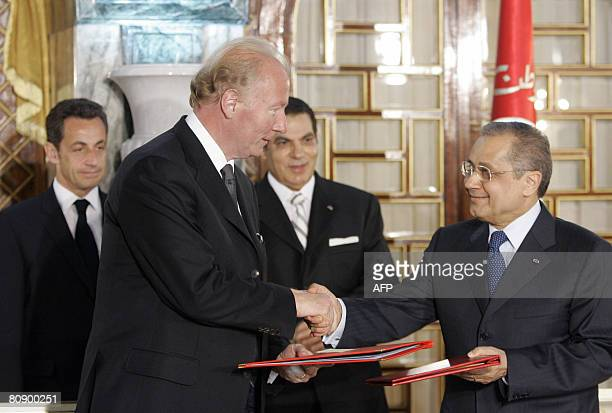 Tunisian Foreign Minister Abdelwahab Abdallah shakes hands with French Immigration Minister Brice Hortefeux after signing a contract as French...