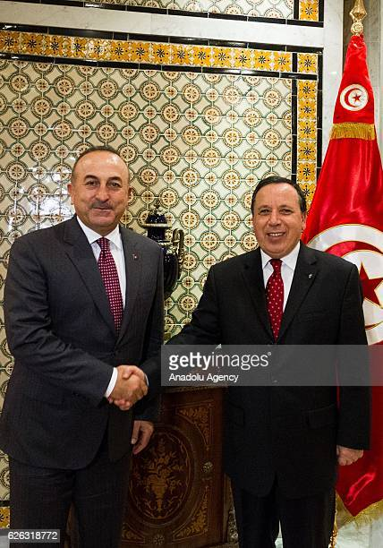 Tunisian Foreign Minister Khamis AlJehinawi welcomes Turkish Foreign Minister Mevlut Cavusoglu in the foreign ministry building in Tunis Tunisia on...