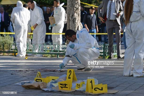 Tunisian forensics inspect the site of a suicide attack in the Tunisian capital Tunis on October 29 2018 A woman suicide bomber blew herself up near...