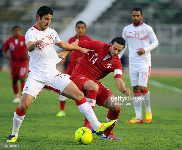 Tunisian forward Mejdi Traoui vies with Peruvian team captain Claudio Pizarro during a freindly football match on February 29 2012 in El Menzh...